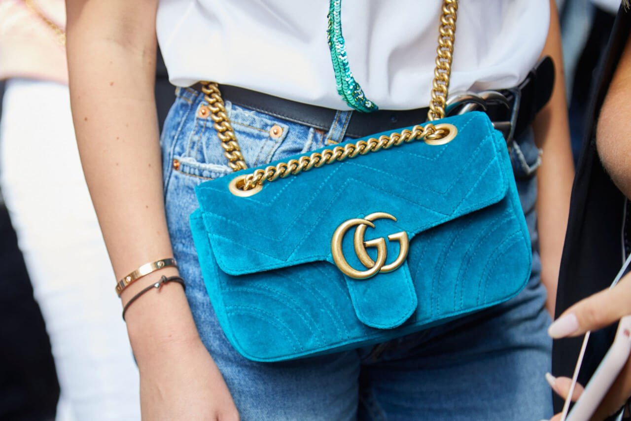 Woman with light blue velvet Gucci bag with golden chain